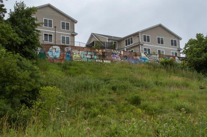 Graffiti covered wall over grassy hillside
