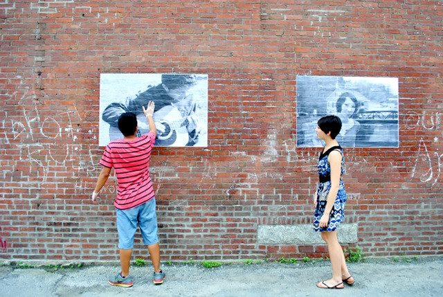 Two people adhering artwork to an exterior brick wall