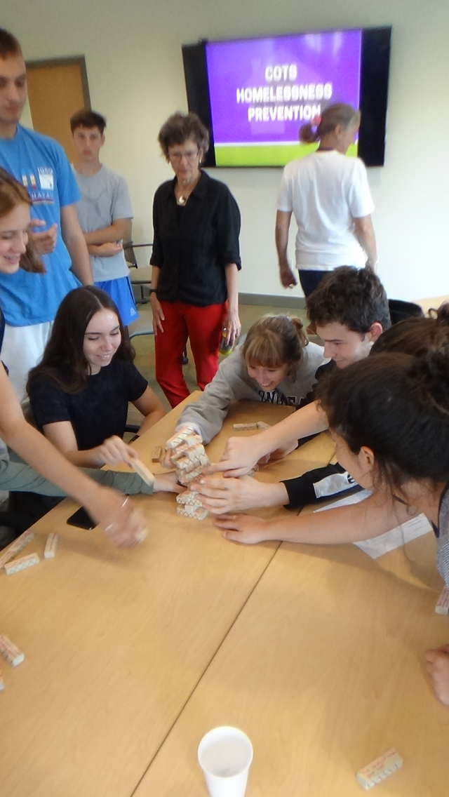 """Students play a new kind of """"Jenga"""" - in which each piece represents the life events that can cause a family to lose their home. A fun game about a terrible reality."""