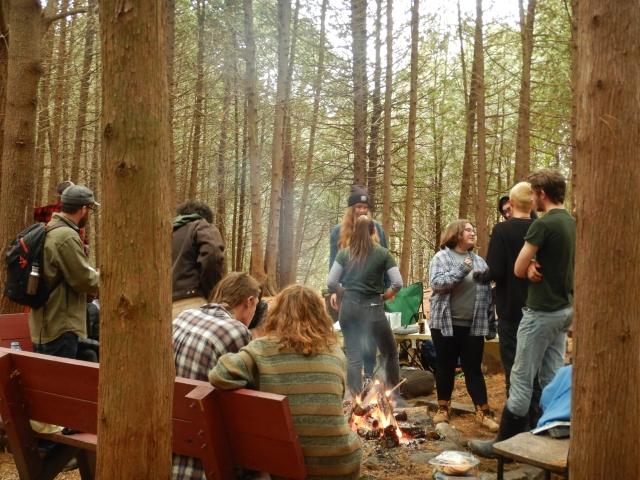 Students gather around a campfire in the woods