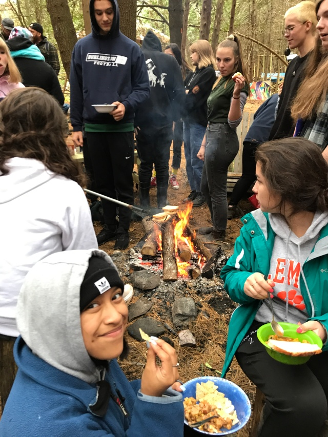 Students cooking and eating around the campfire