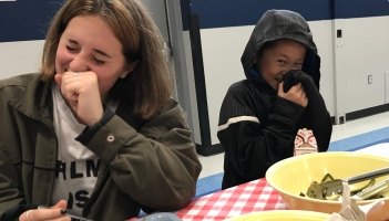 High school student and kindergartner laughing over lunch