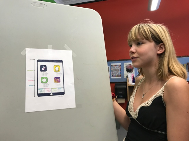 Student stands next to data chart composed of phone app icons