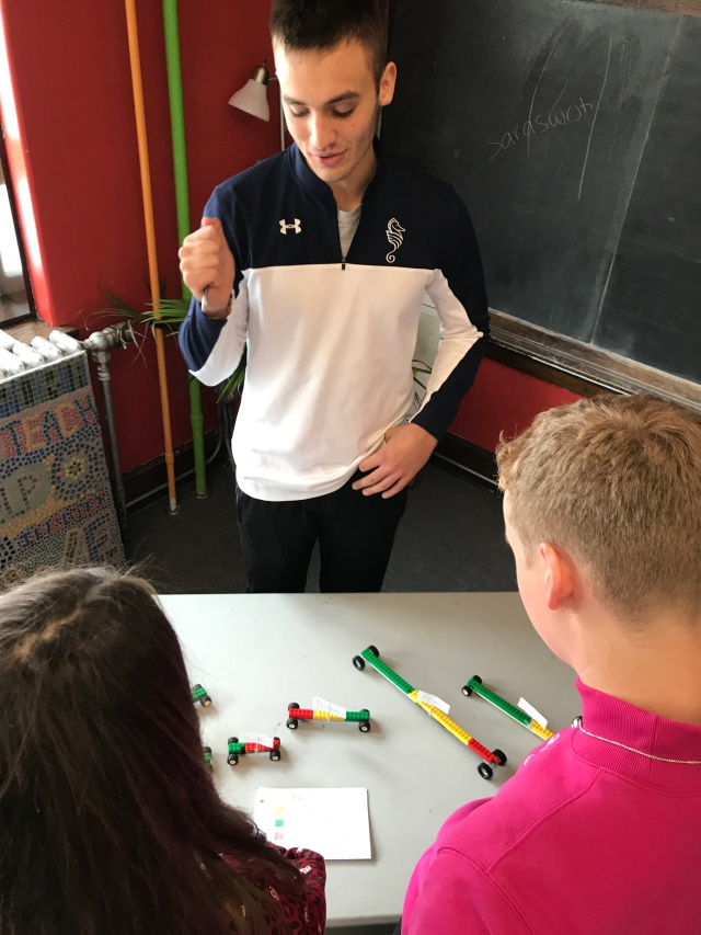 Student stands over lego cars presenting data