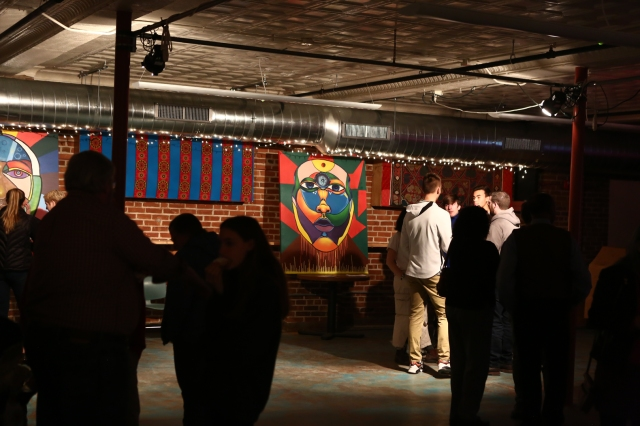 Students and others mingle in event space in front of painting