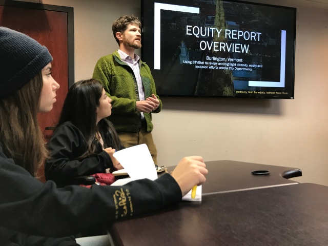 "Man standing in front of screen displaying ""Equity Report Overview"""