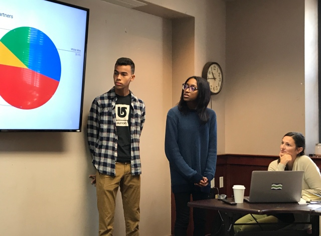 Students present data to woman at desk