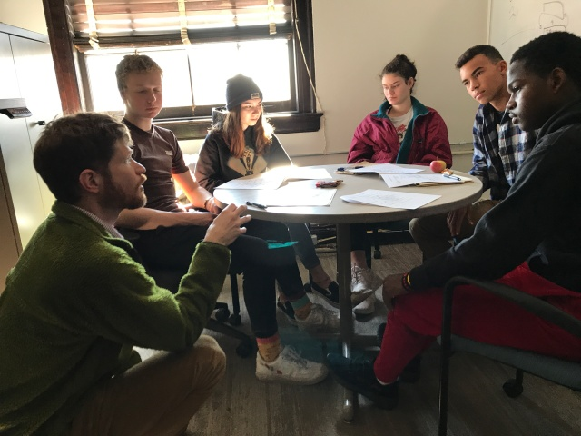 Students sit around the table with an adult kneeling down and engaging in conversation