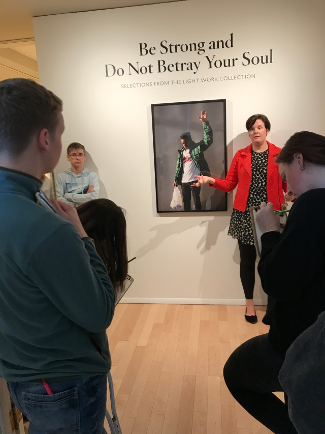Woman standing in front of art photograph as students look on