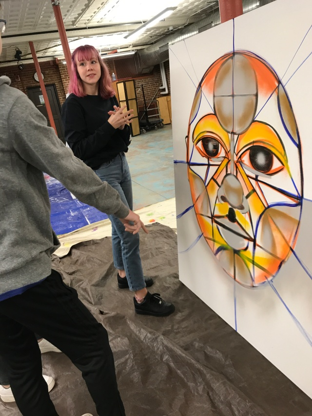 Student standing in front of large painting of face