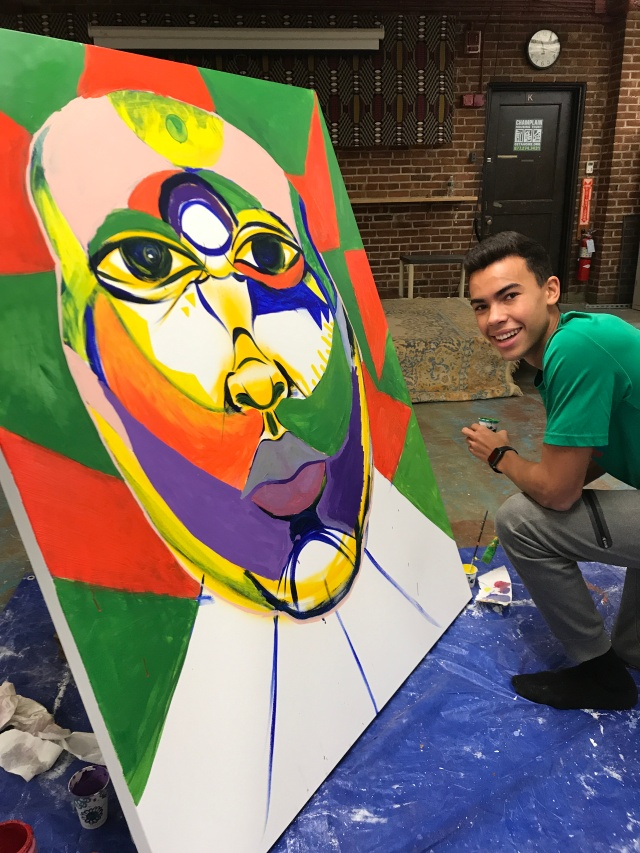 Student in front of large canvas with face
