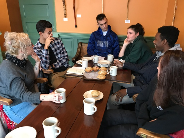 Students sit around talking and laughing over coffee and muffins with local artist