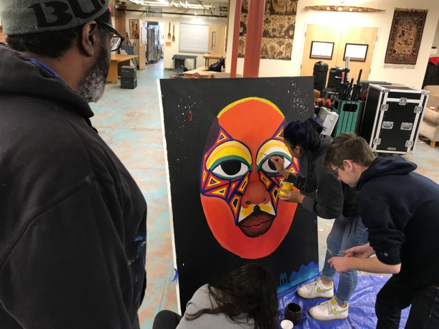 Students paint canvas as mentor artist looks on