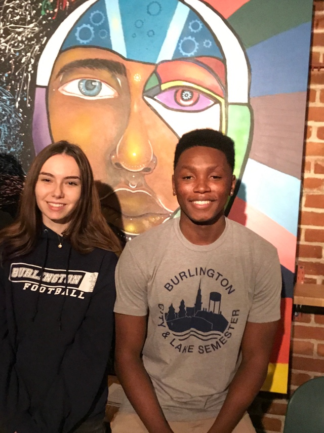 Two students in front of painting of face