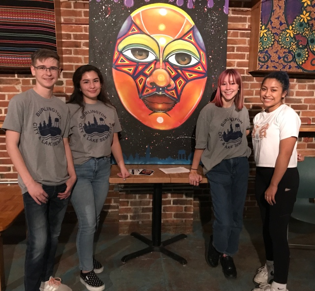 Four students in front of painting