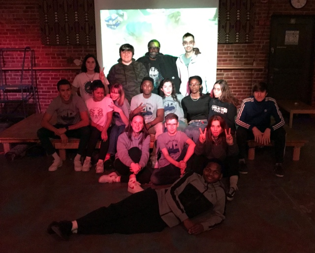 Group shot of students with artist in front of projection