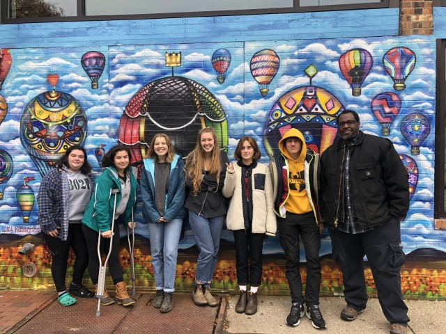 Artist and students in front of colorful hot air balloon mural
